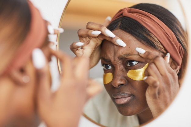 Portrait of young african-american woman doing skincare routine at home and popping zit while looking at mirror, copy space