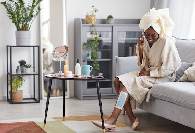 Portrait of young african-american woman enjoying beauty routine at home with focus on wax strips on leg, copy space
