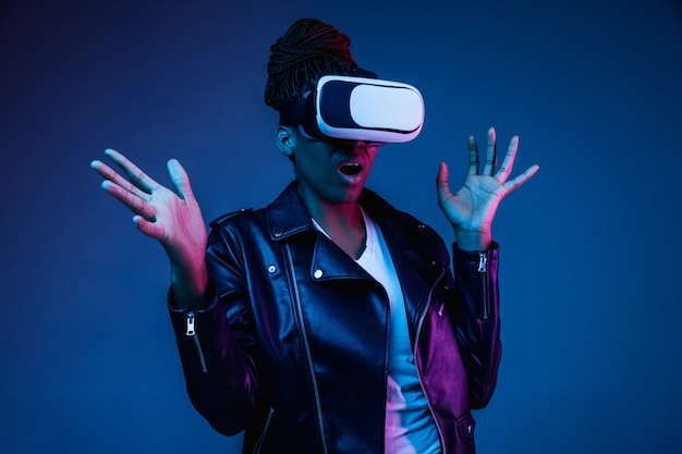 Portrait of young african-american woman playing in vr-glasses in neon light on blue.