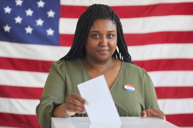 Portrait of young african-american woman putting vote bulletin in ballot box and  while standing against american flag on election day, copy space