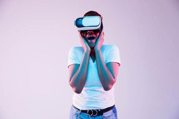 Portrait of young african-american woman's playing in vr-glasses in neon light on gradient background. concept of human emotions, facial expression, modern gadgets and technologies. look astonished.