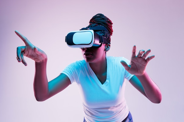 Portrait of young african-american woman's playing in vr-glasses in neon light on gradient background. concept of human emotions, facial expression, modern gadgets and technologies. pointing on.