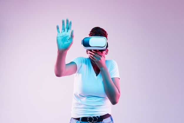Portrait of young african-american woman's playing in vr-glasses in neon light on gradient background. concept of human emotions, facial expression, modern gadgets and technologies. touches something.