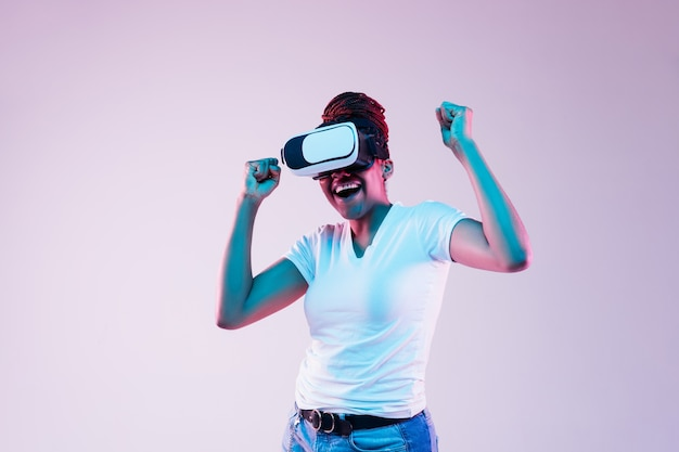Portrait of young african-american woman's playing in vr-glasses in neon light on gradient background