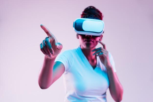 Ritratto di giovane donna afro-americana che gioca in occhiali vr in luce al neon su sfondo sfumato