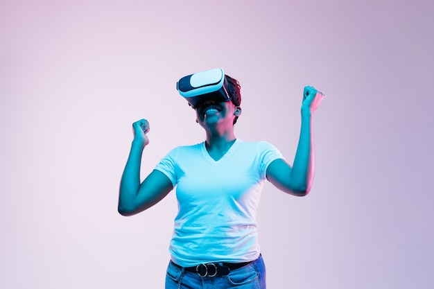 Portrait of young african-american woman's playing in vr-glasses in neon light on gradient.