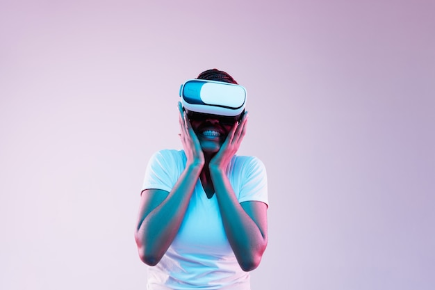 Portrait of young african-american woman's playing in vr-glasses in neon light on gradient
