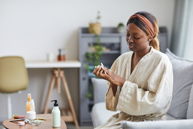 Portrait of young african-american woman using hand cream or moisturizer, skincare and beauty routine concept, copy space