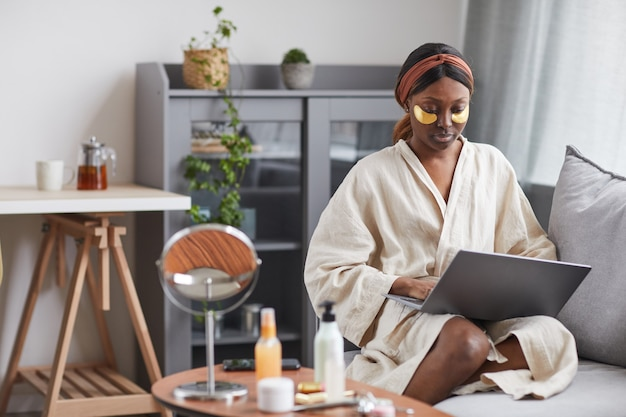 Portrait of young african-american woman using laptop while enjoying skincare routine at home and relaxing, copy space