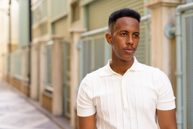 Portrait of young african businessman wearing casual clothes at city street while thinking