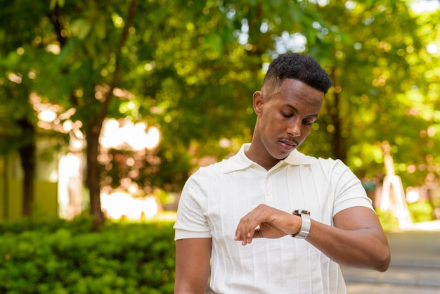 Portrait of young african businessman wearing casual clothes and looking time from wristwatch at park