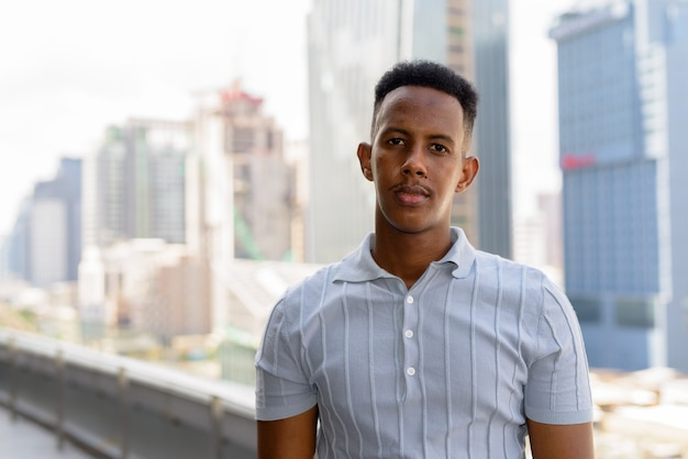 Portrait of young african businessman wearing casual clothes at rooftop in city