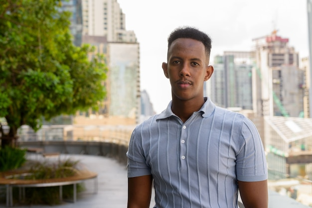 Portrait of young african businessman wearing casual clothes at rooftop garden