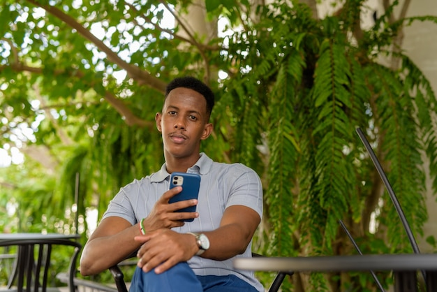 Portrait of young african businessman wearing casual clothes and sitting at coffee shop while holding mobile phone