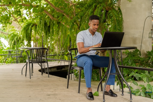 Portrait of young african businessman wearing casual clothes and sitting at coffee shop while using laptop computer and social distancing