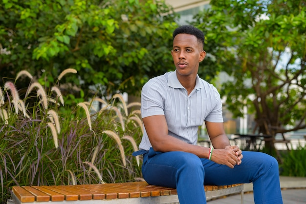 Portrait of young african businessman wearing casual clothes and sitting at park bench while thinking