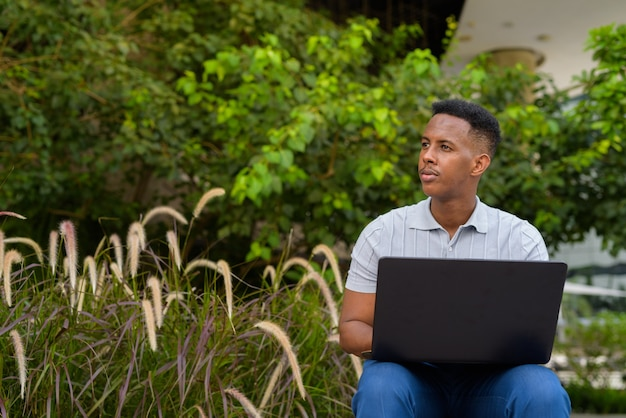 Portrait of young african businessman wearing casual clothes and sitting at park bench while using laptop computer