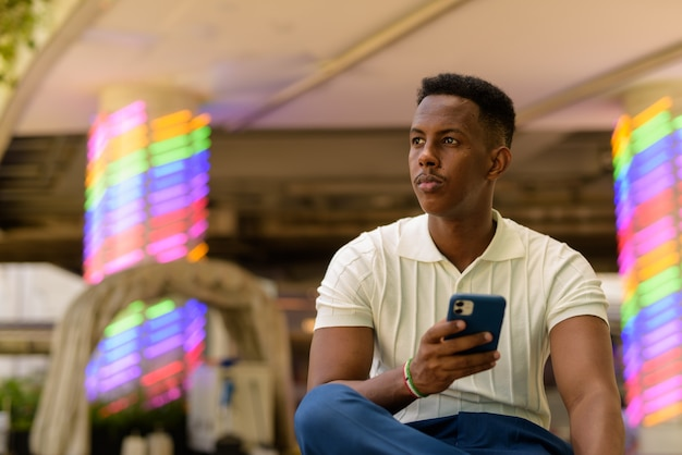 Portrait of young african businessman wearing casual clothes and using mobile phone while sitting