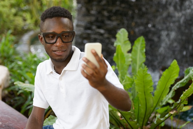 Portrait of young african man against view of the garden in nature outdoors