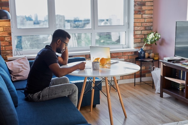 Portrait of young african man concentrated on work at home