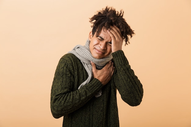 Portrait of a young african man dressed in autumn clothes isolated over beige wall, suffering from a headache