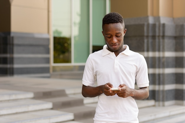 Portrait of young african man at modern building in the city outdoors