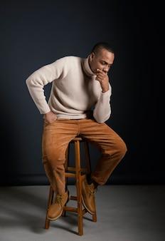 Ritratto giovane africano uomo seduto su una sedia