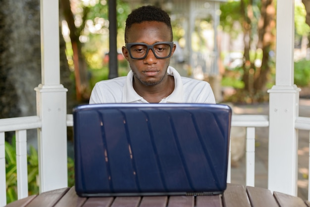 Portrait of young african nerd man as student with eyeglasses at the park outdoors