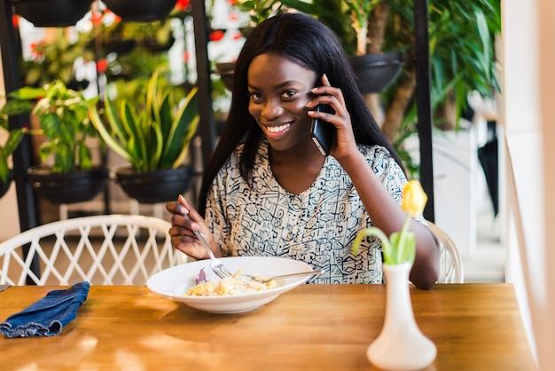 Ritratto di giovane donna africana che mangia pasta degli spaghetti e parla al telefono