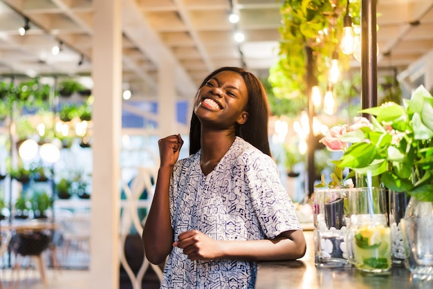 Portrait of young african woman standing in cafe