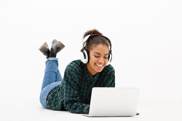 Portrait of young african woman with laptop on white