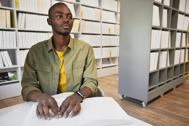Portrait of young africanamerican man reading braille book in college library copy space