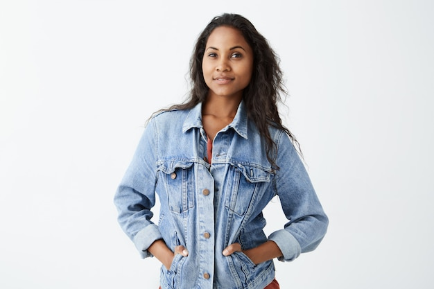 Portrait of young afro-american girl with dark skin wearing denim jacket and red t-shirt  with serious expression, standing with her hands in pockets. dark-skinned female model with d