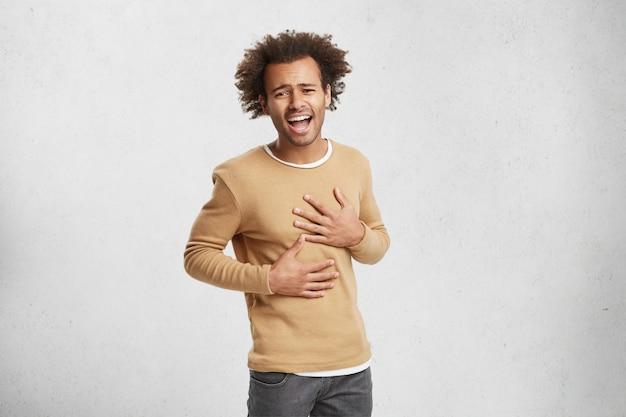 Ritratto di giovane uomo afroamericano non riesce a smettere di ridere, tiene le mani sullo stomaco