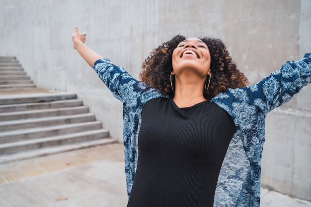 Portrait of young afro american woman standing outdoors with arms raised and laughing.