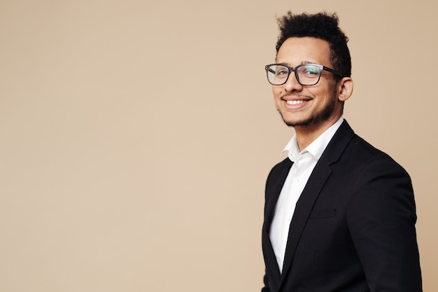Portrait of young afro businessman wearing shirt, black suit, glasses and looking at front while standing at beige wall