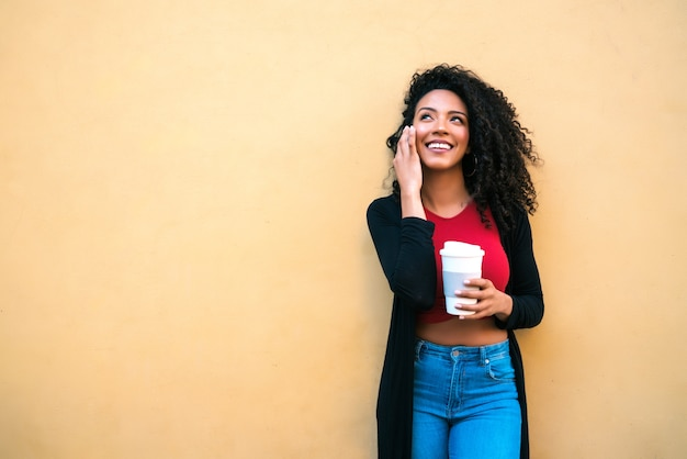 Portrait of young afro woman talking on the phone while holding a cup of coffee against yellow background. communication concept.