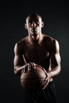 Portrait of young afroamerican basketball player, preparing to throw ball