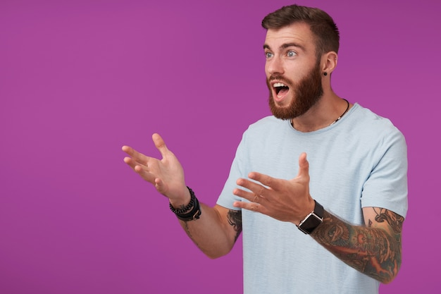 Portrait of young agitated brunette male with beard watching football on tv and being excited about game, looking aside with raised hands while posing on purple