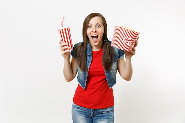 Portrait of young amazed beautiful woman in casual clothes watching movie film, holding bucket of popcorn and plastic cup of soda or cola isolated on white background. emotions in cinema concept.