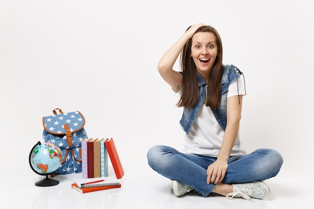 Portrait of young amazed excited woman student in denim clothes clinging to head, sitting near globe, backpack, school books isolated