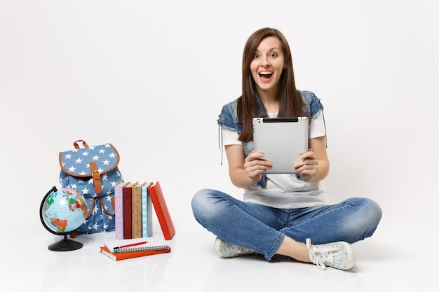 Portrait of young amazed surprised woman student holding using tablet pc computer, sitting near globe, backpack, school books isolated on white wall