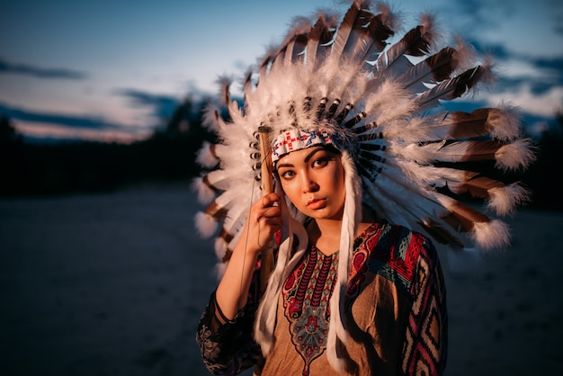 Portrait of young american indian woman on sunset. cherokee, navajo, west native culture. headdress made of feathers of wild birds.