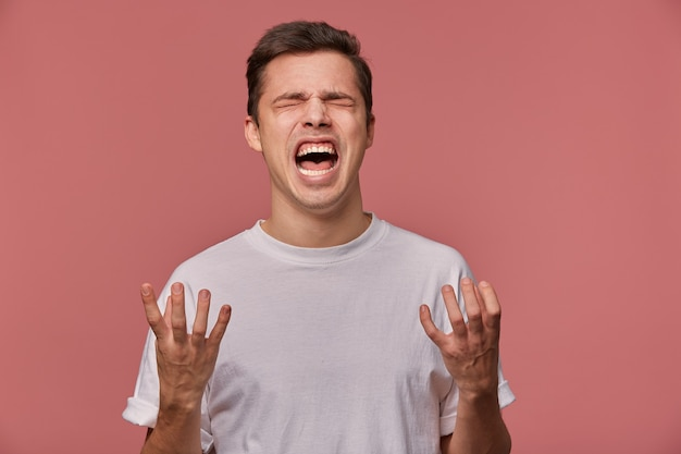 Portrait of young angry guy in blank t-shirt, hears bad news and looks evil, stands on pink and screaming with unhappy expression.