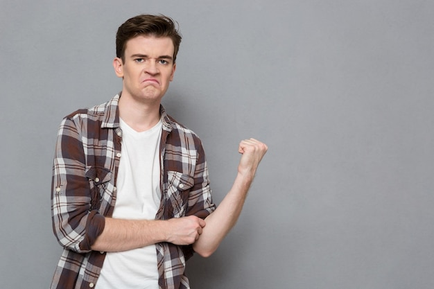 Portrait of a young angry man showing fist over gray wall