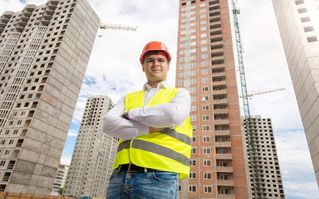 Portrait of young architect in hardhat and safety vest posing against new buildings