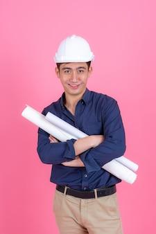 肖像若い建築家の男の身に着けているヘルメットとホールドブループリント