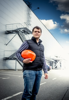 Portrait of young architect posing with hardhat against industrial building
