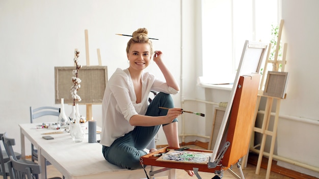Portrait of a young artist on the side, a girl draws on canvas in the studio