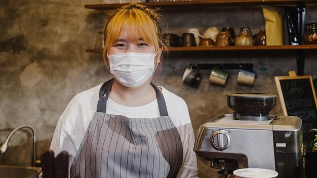 Ritratto giovane ragazza asiatica cameriera indossare maschera medica sensazione sorriso felice in attesa di clienti dopo il blocco al caffè urbano.